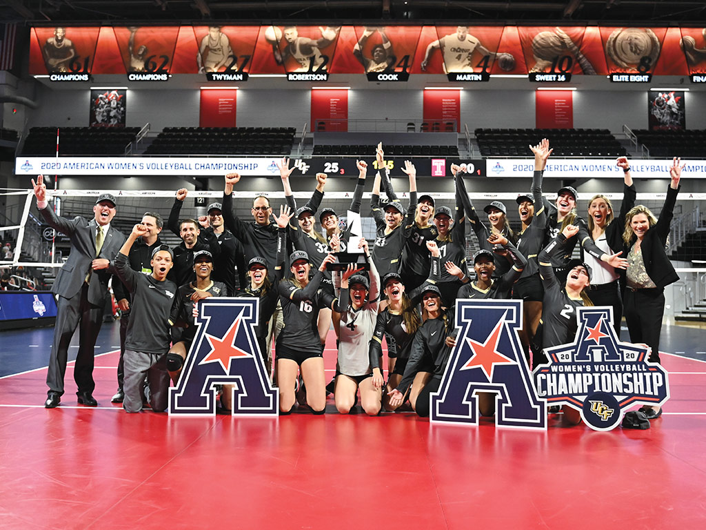 Volleyball team gathers for a photo in front of the net on the court while holding American Athletic Conference champions signs