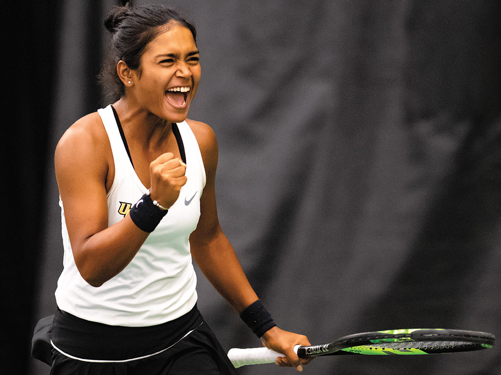 Women's tennis player clinches fist in celebration on the court