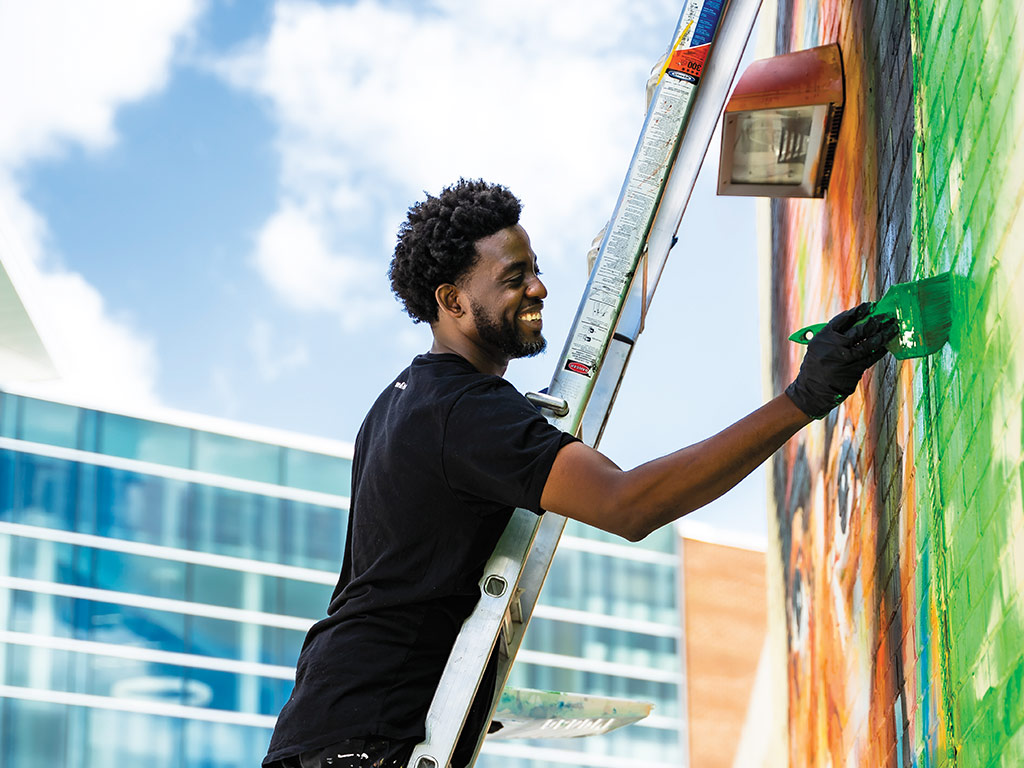Peterson Guerrier smiles while painting