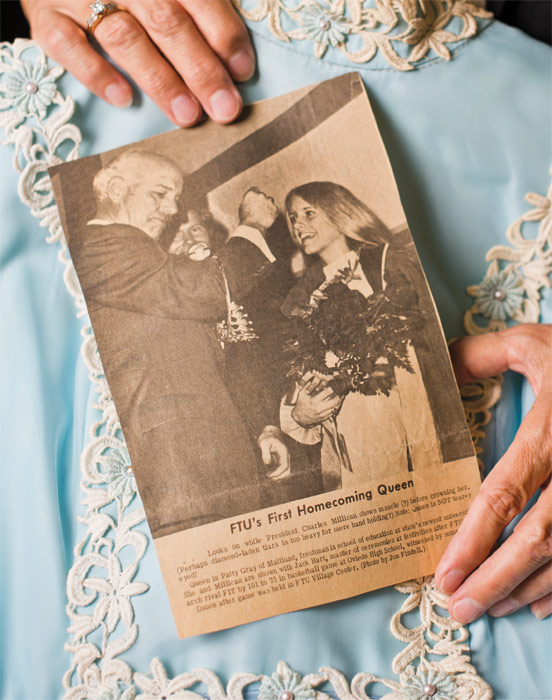 A newspaper clipping about the crowning of the first Homecoming Queen, held in front of Patty Gray Neff's dress.