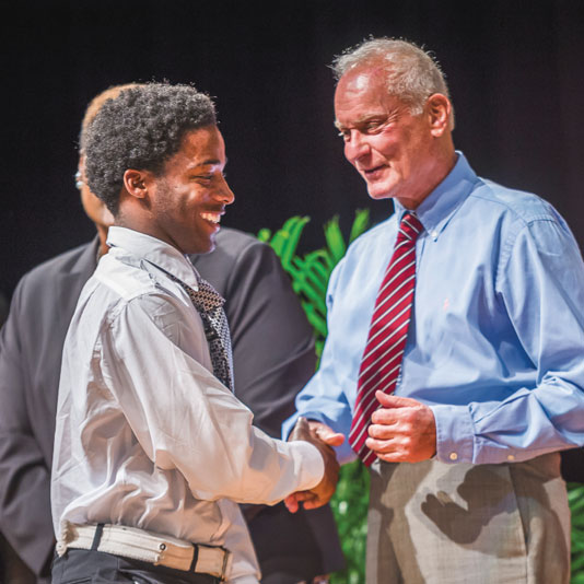 Harris Rosen shaking boy's hand on stage