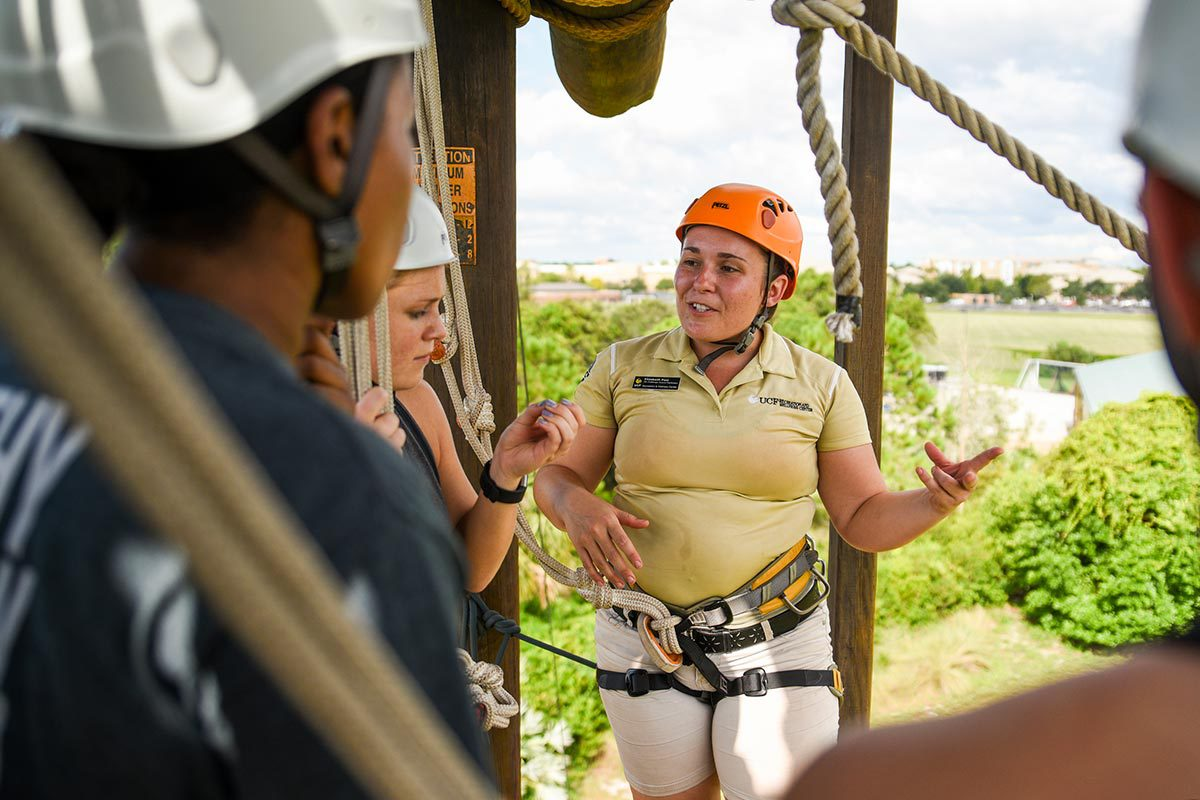 A woman wearing an orange helmet speaks to a small group of people as she provides instructions for completing the high-elements course.