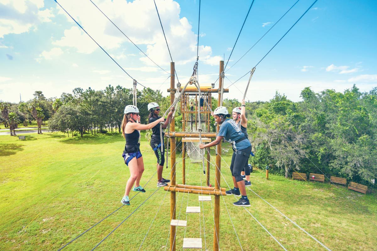 Four people in helmets hold onto ropes as they try to cross wires suspended in the air to complete a high-elements climbing course.