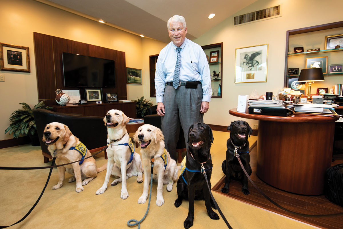 An older man stands in his office with a wide smile on his face. In front of him are three yellow labs and two black labs.