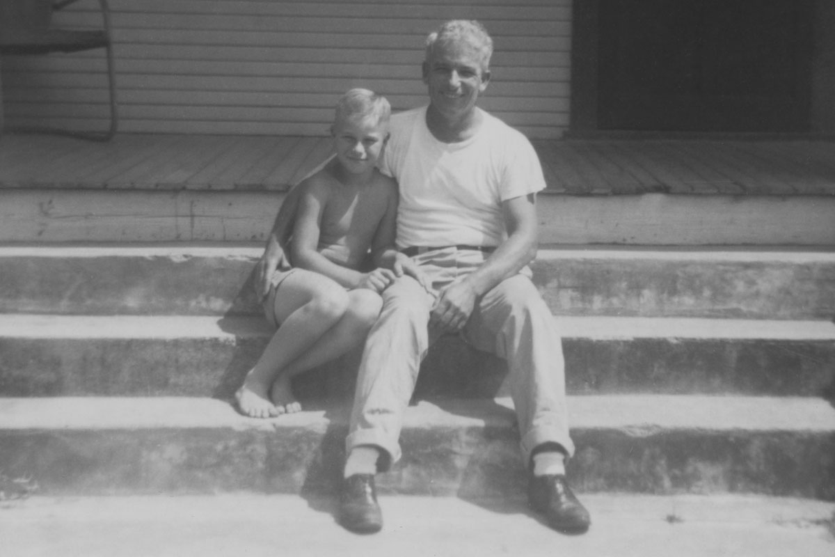 A black and white photo of a young, shirtless, white boy sitting next to an older white man, who has his arm around the younger boy, on the steps.