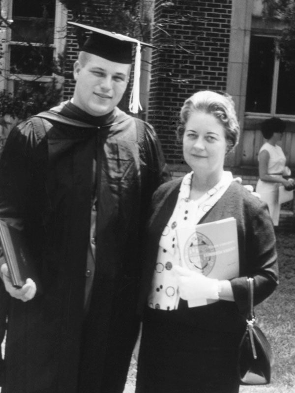 A black and white photo of man in academic regalia, including cap, gown and hood, standing next to an older woman.