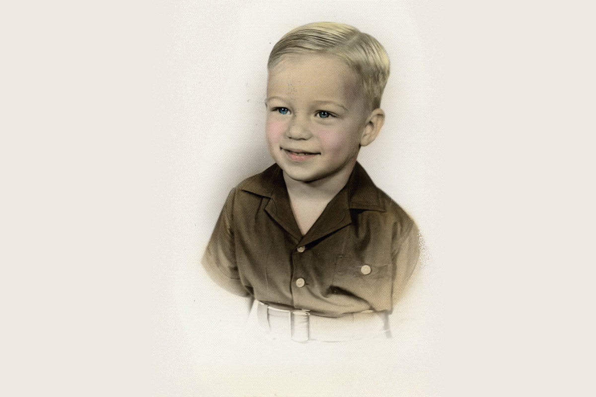 A colorized black and white photo of young white boy with blonde hair, blue eyes, and rosy cheeks wears a brown button-up shirt.