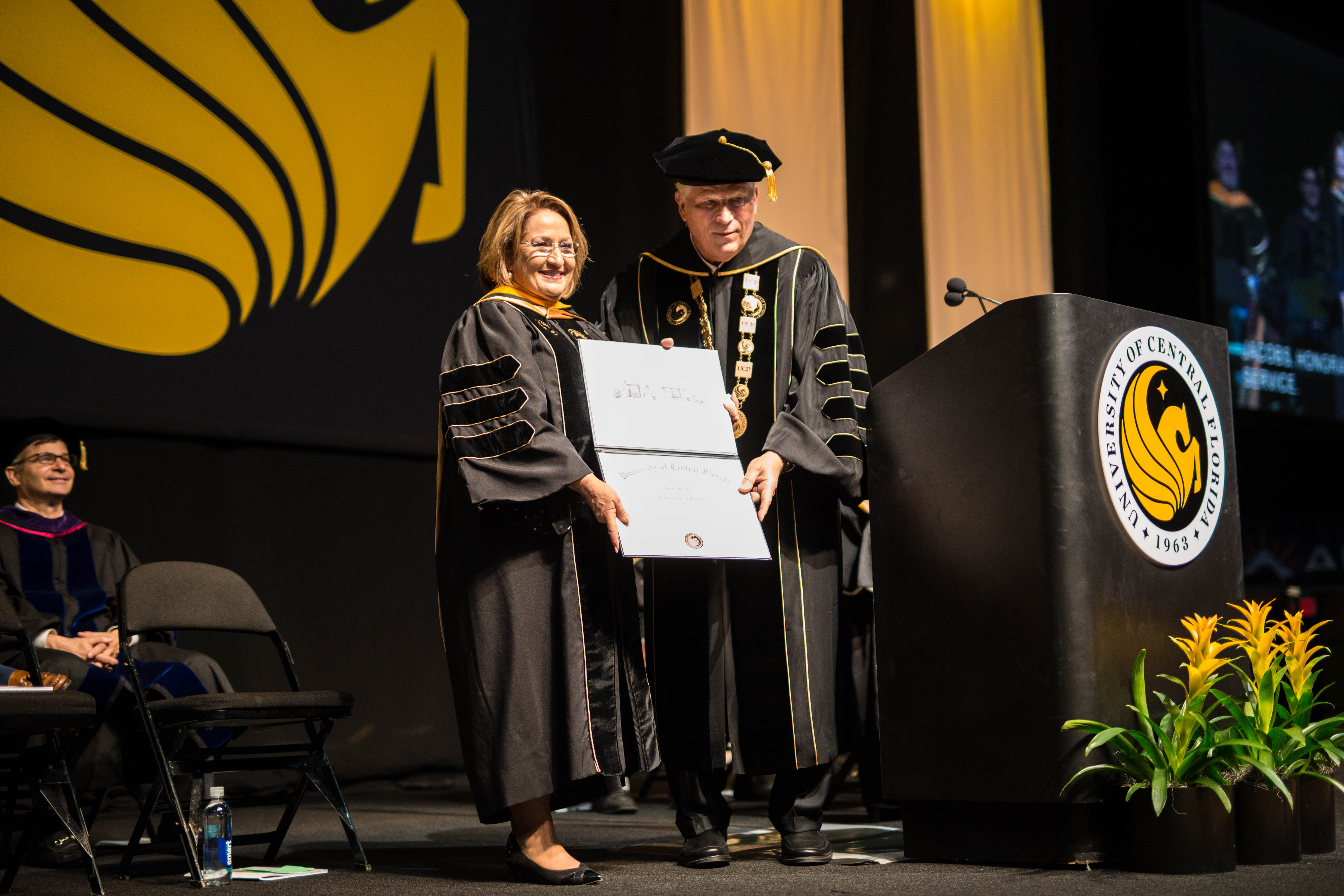 Orange County Mayor Teresa Jacobs holds a honorary diploma as John C. Hitt presents it to her own stage.