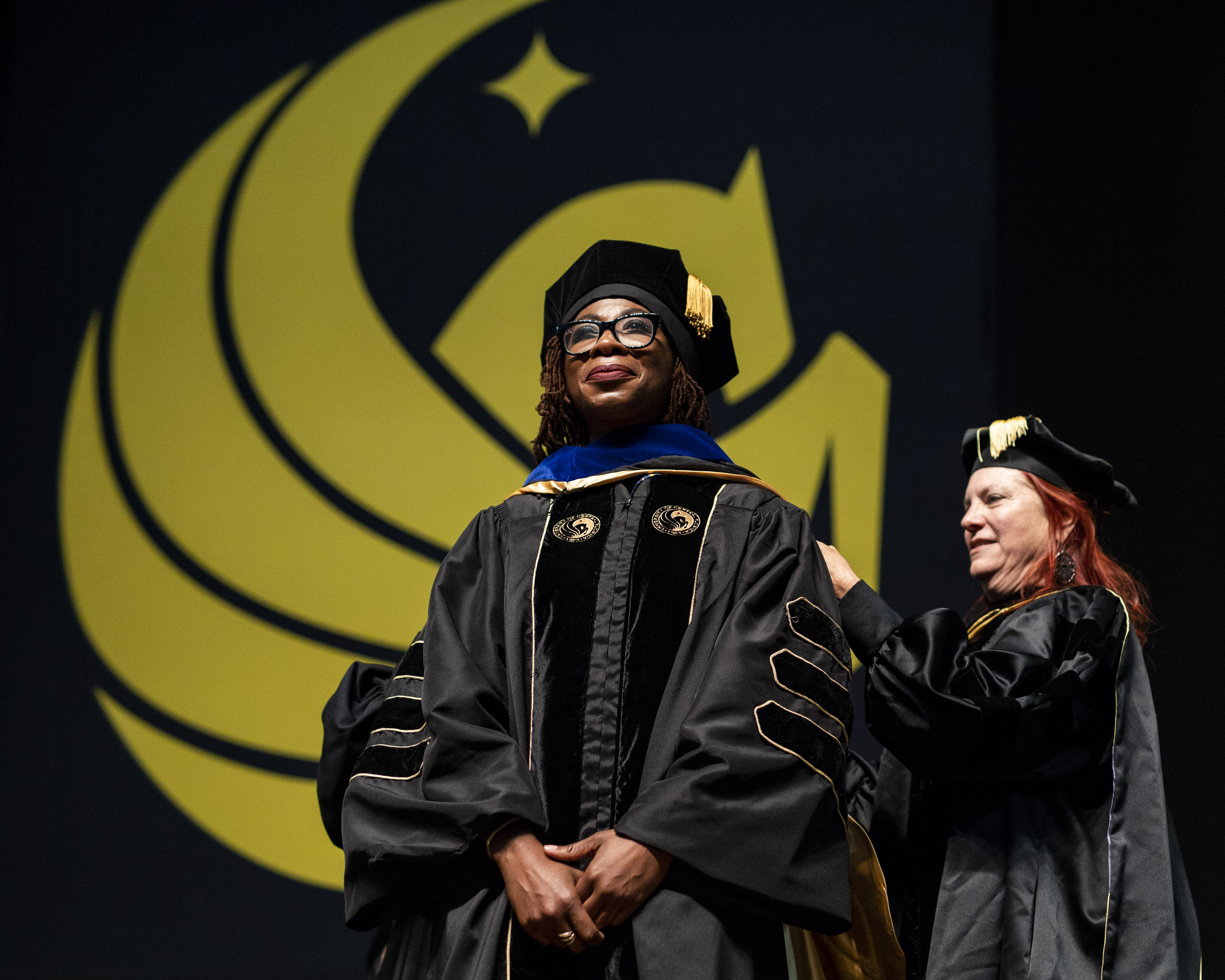A female doctoral candidate waits on stage as a woman places a hood over her.