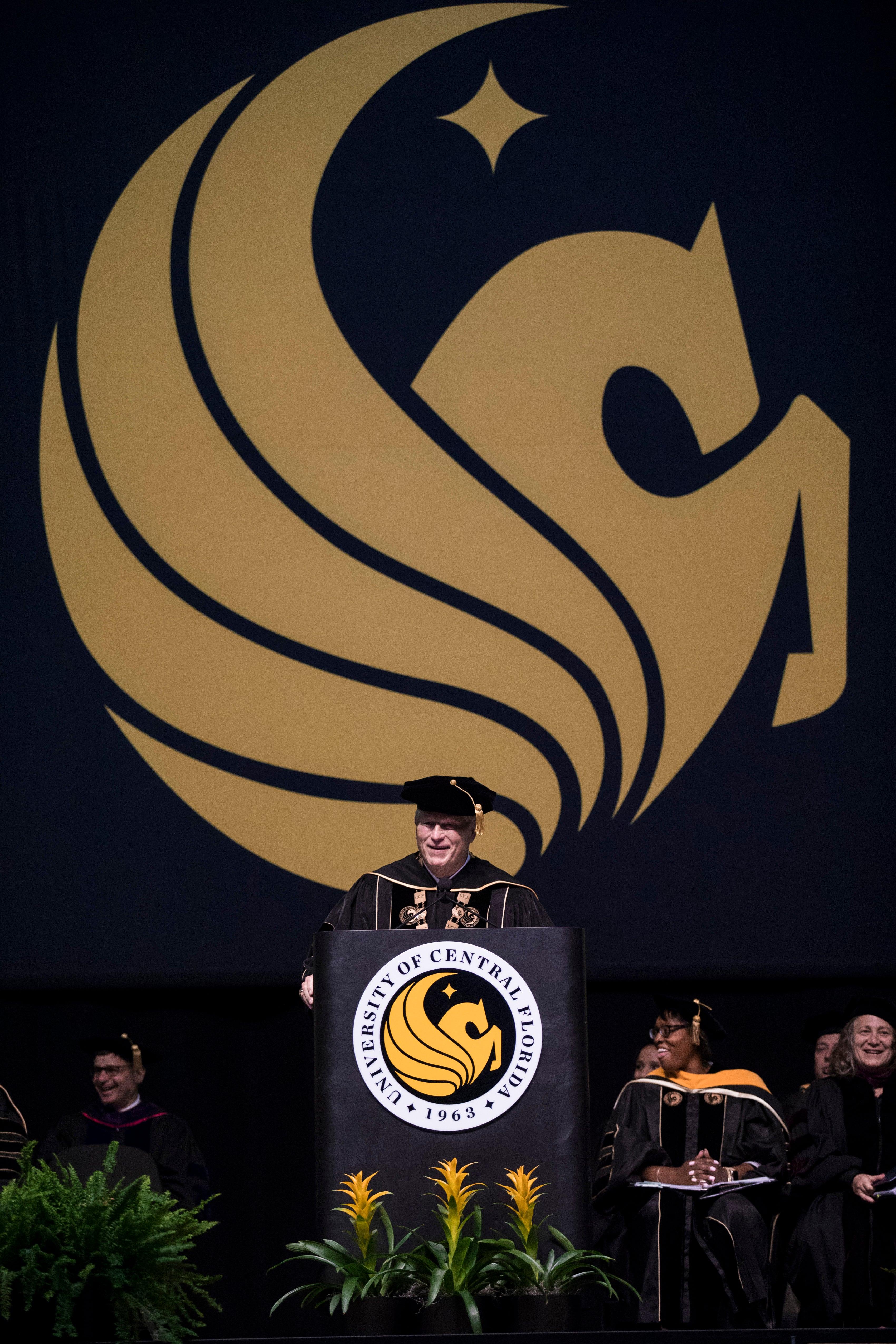 John C. Hitt speaks at a podium while wearing regalia as a yellow Pegasus symbol hangs behind him.