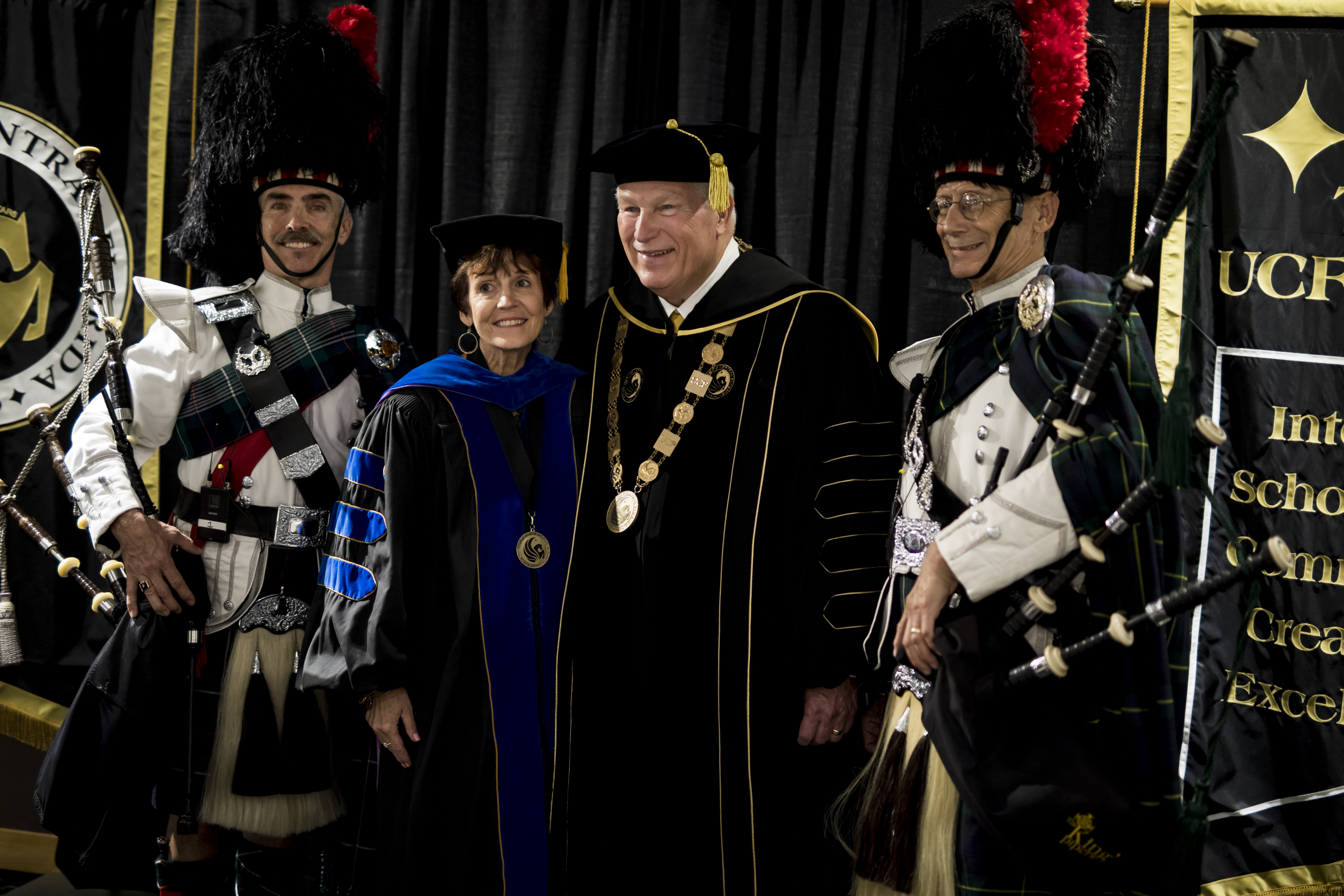 John C. Hitt poses beside a woman as two bagpipe players stand on either side of them for a photo.