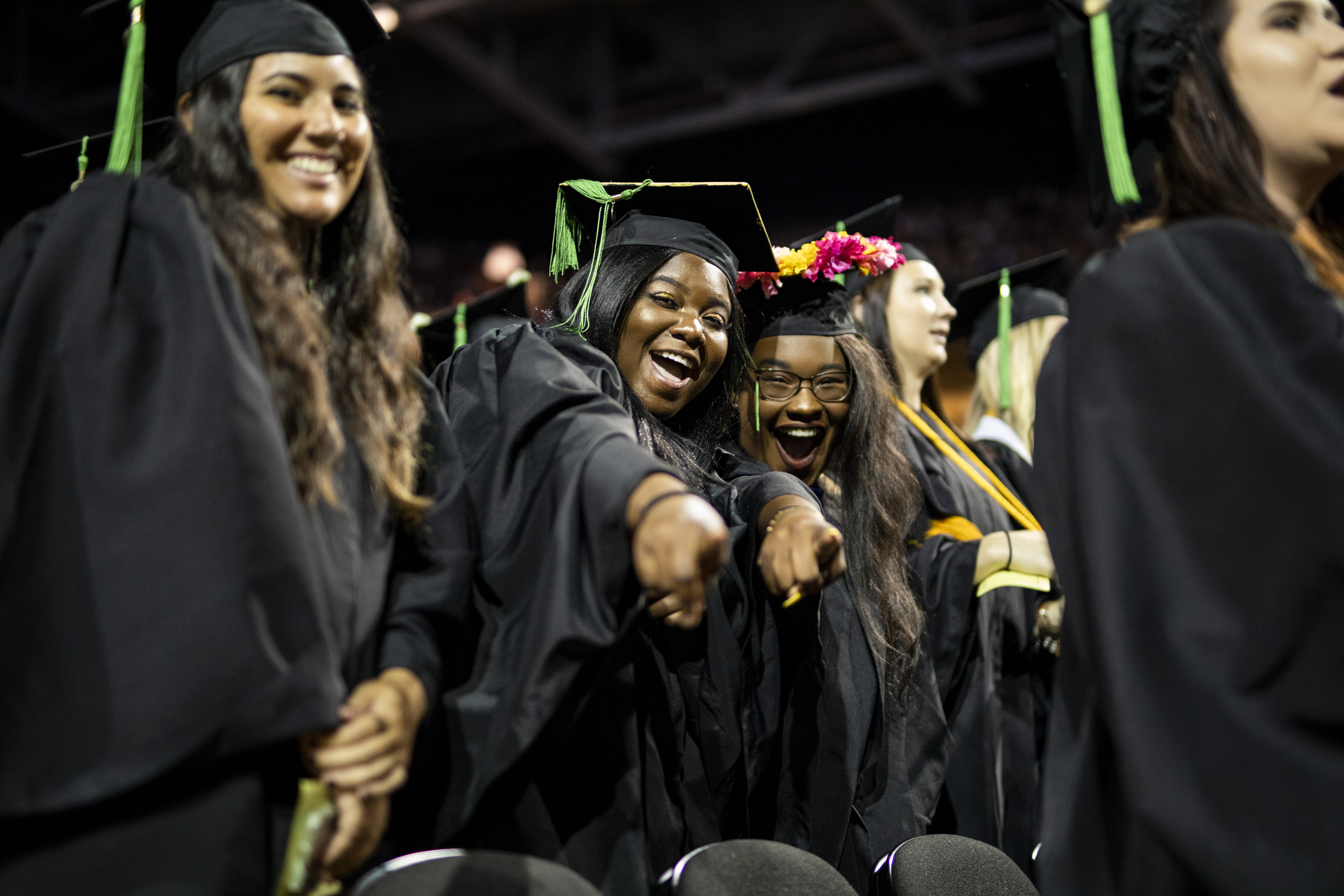 Two students wearing caps and gowns smile and point at the camera during a graduation ceremony.