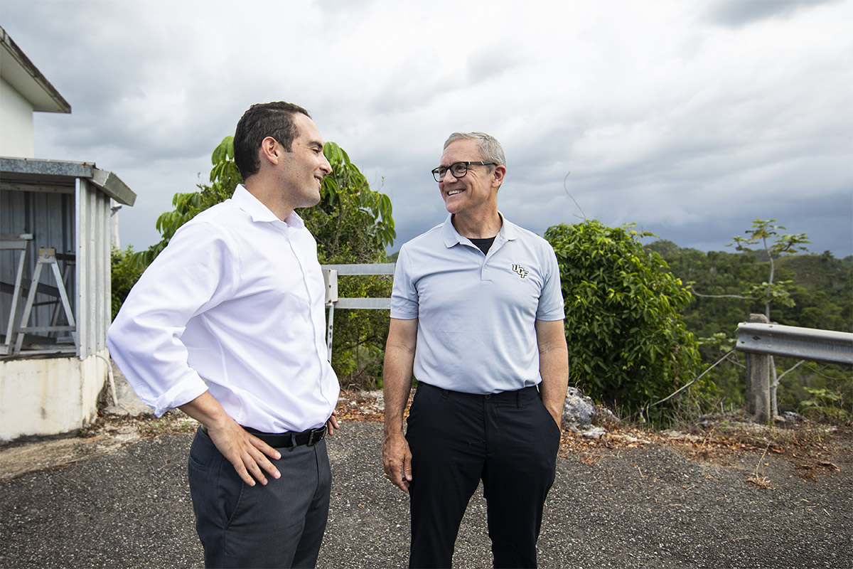 President Dale Whittaker wearing grey UCF polo, black pants and glasses, smiling at man with white shirt, grey pants, and his hands on his hips at Arecibo.