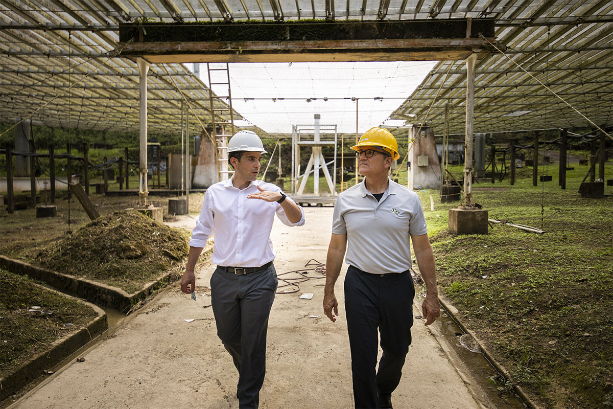Concerned President Dale Whittaker walking with man talking about Arecibo and using hand gestures, both wearing hard hats.