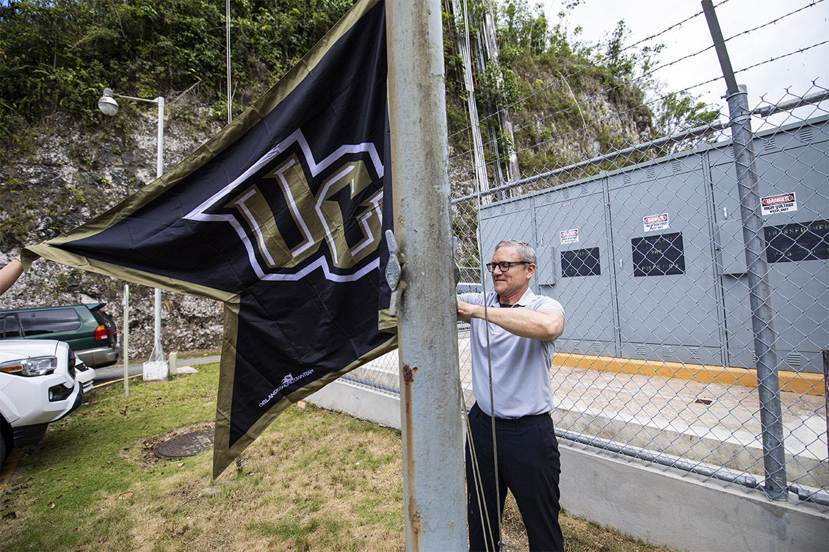 President Dale Whittaker putting up ucf flag at Arecibo.