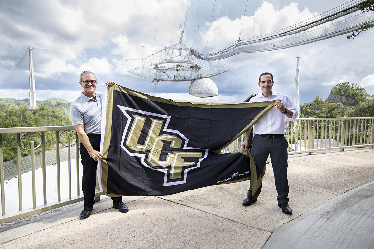 President Dale Whittaker and man holding up black and gold ucf flag at Arecibo.