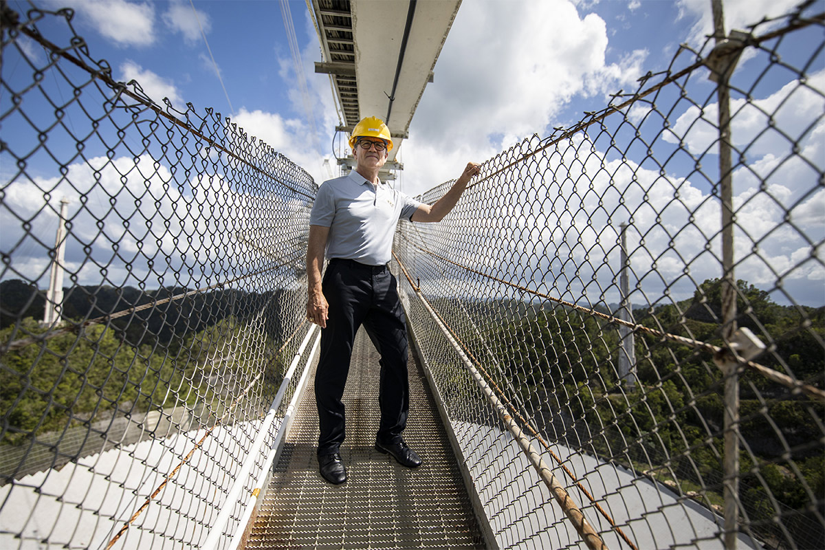 President Dale Whittaker standing on a suspension bridge over Arecibo.