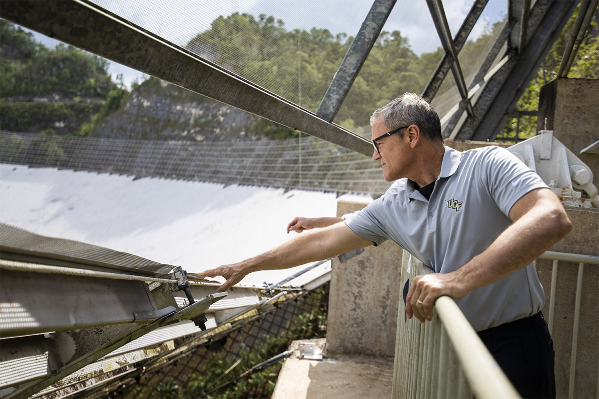 President Dale Whittaker reaches over guard rail to touch materials near Arecibo.
