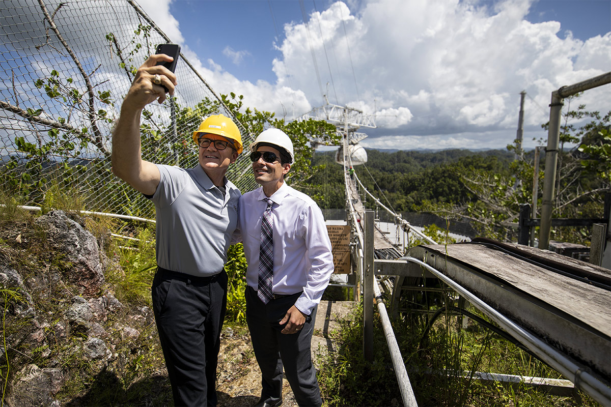 President Dale Whittaker wearing a grey polo, yellow hard hat takes a selfie with man wearing purple shirt, plaid tie, sunglasses and a white hard hat in Arecibo complex.