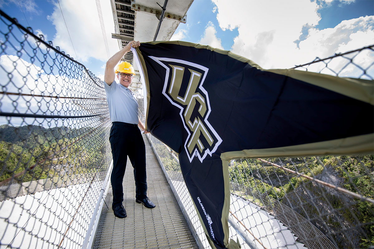 A man in a polo and hardhat holds up a giant black UCF flag.