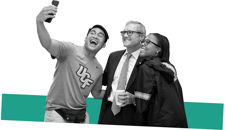 Dale Whittaker posing for a selfie with two students
