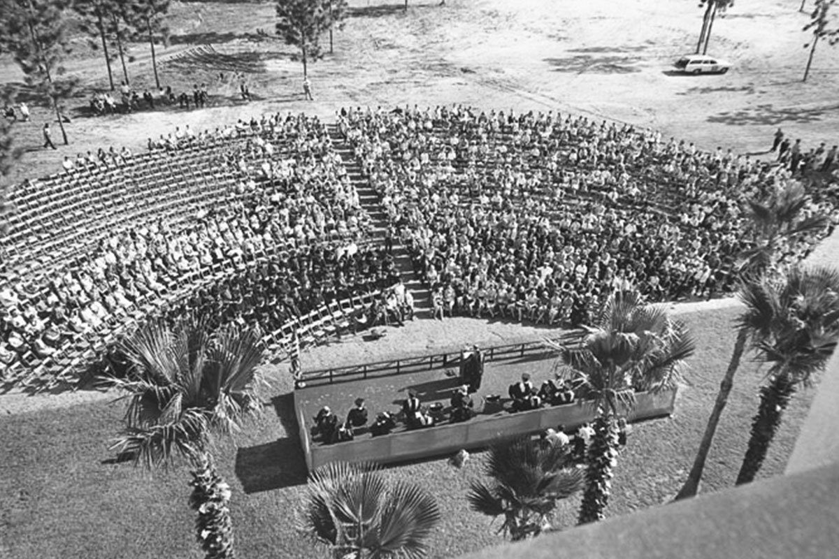 A black and white overhead shot shows a large crowd outside while a man speaks at a podium.