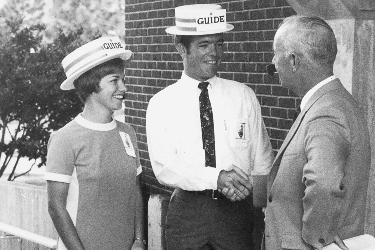 A black and white image shows two students wearing hats while one shakes hands with a man in a suit.