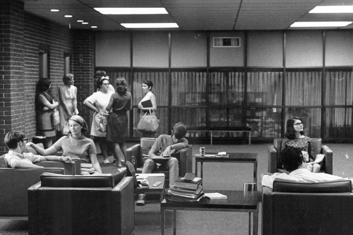 A black and white image shows a group of students standing at the back of a room, while others sit in chairs with books.