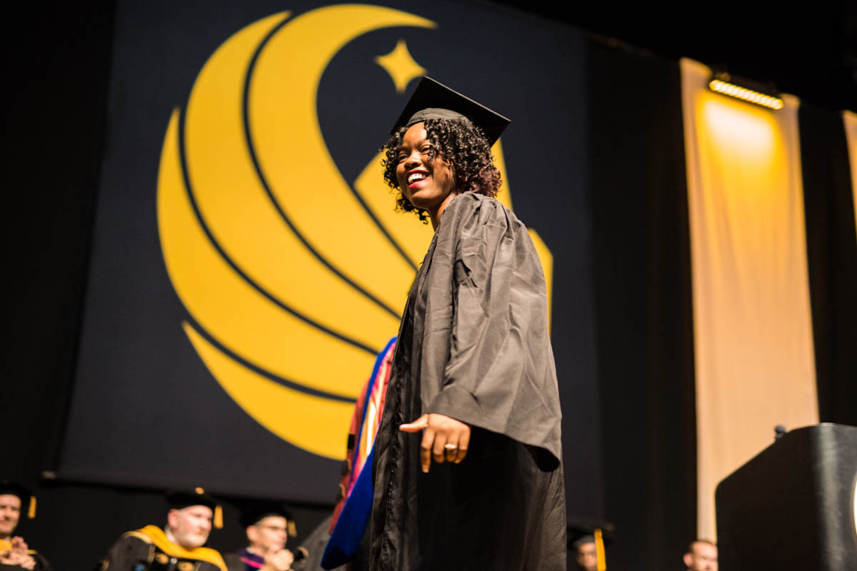 A woman in a cap and gown walks across the stage with a yellow pegasus symbol in the background.
