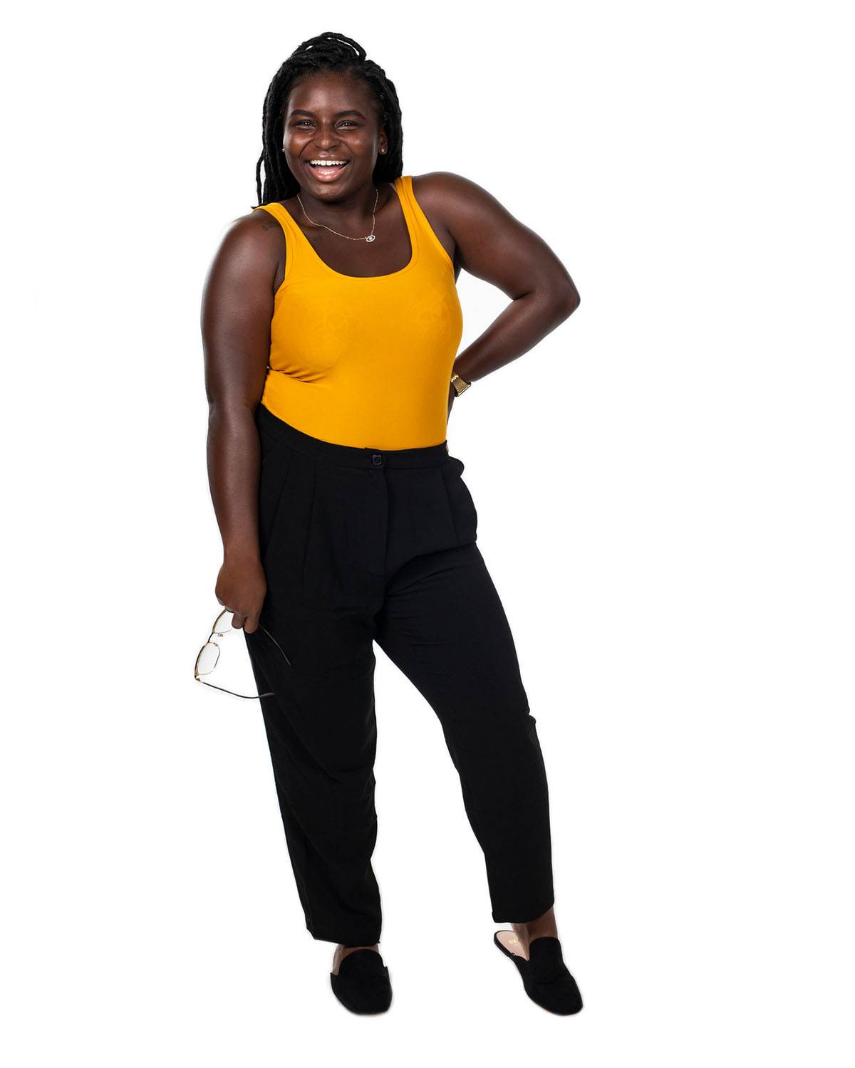 A woman in an orange tank top and black pants holds her glasses with one hand on her hip as she smiles.