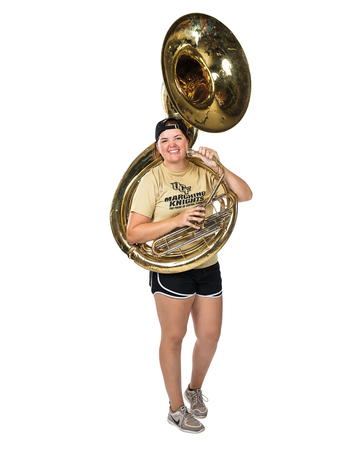 A woman in a yellow shirt and black shorts holds a tuba across her body as she smiles.