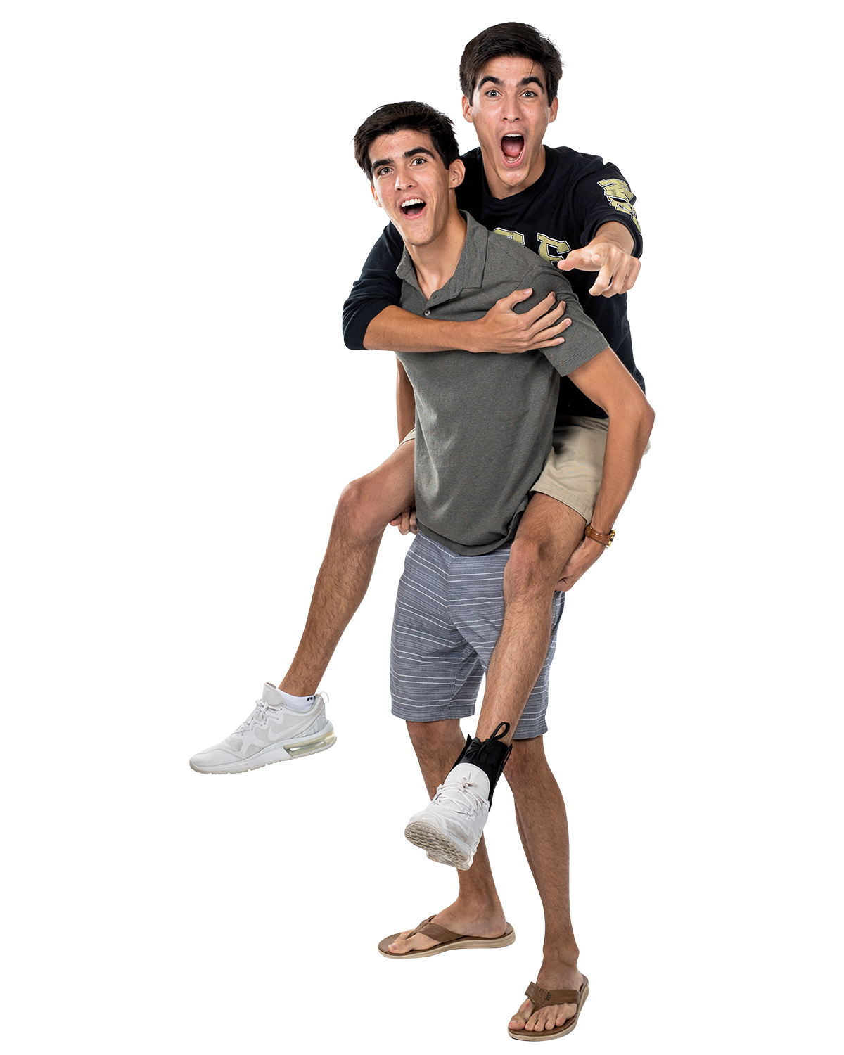A man holds his twin who is pointing at the camera on his back.