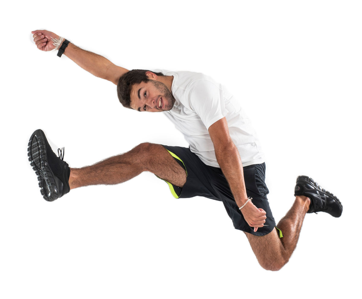 A man in a white shirt and black shorts jumps into the air as he stretches his arms.
