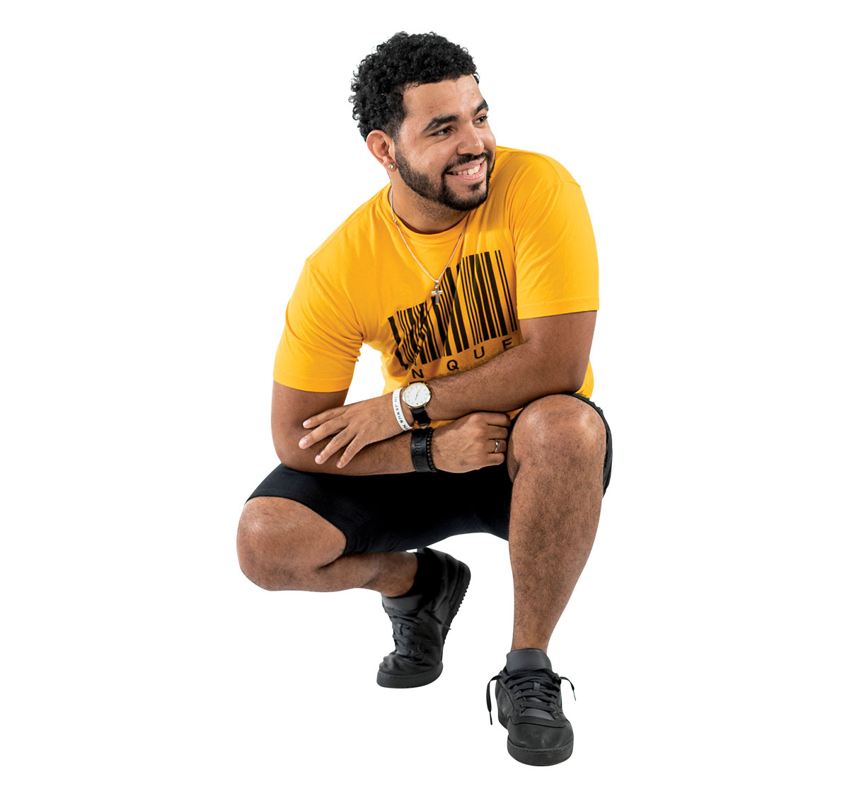 A man in a yellow shirt and black shorts crouches down while he looks to the side and smiles.