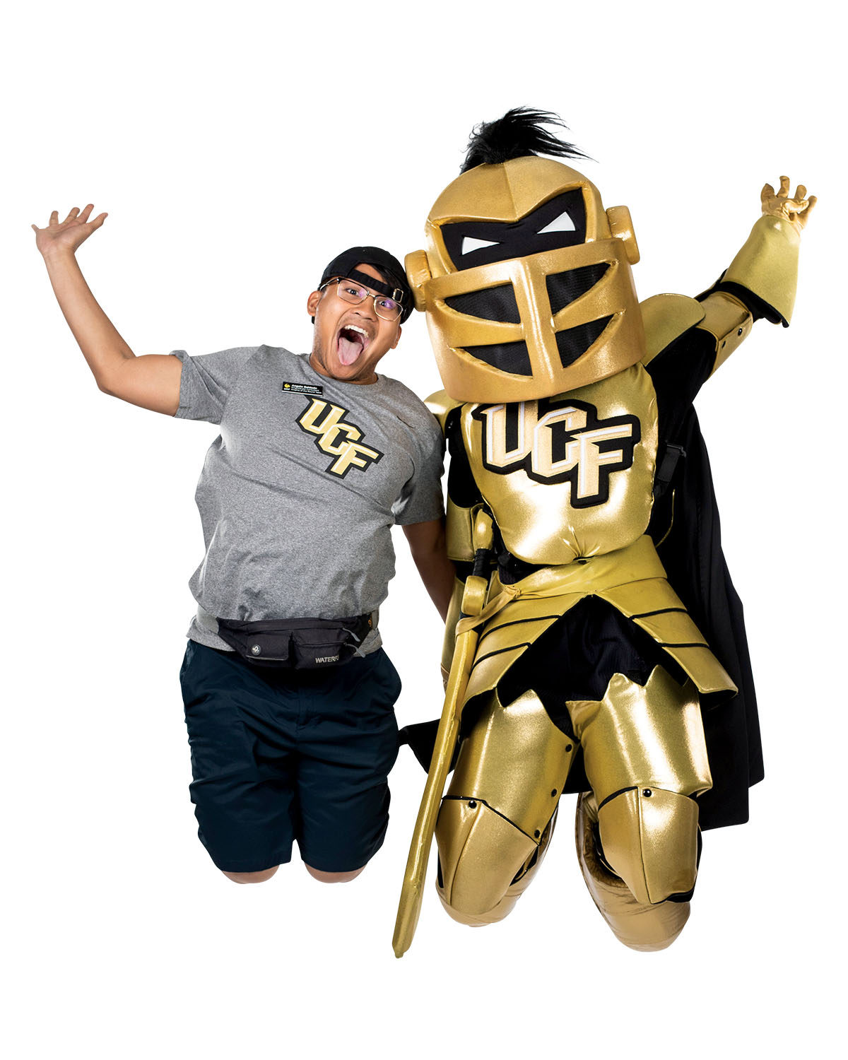 A man wearing a grey UCF shirt jumps in the air along someone in a knight costume.