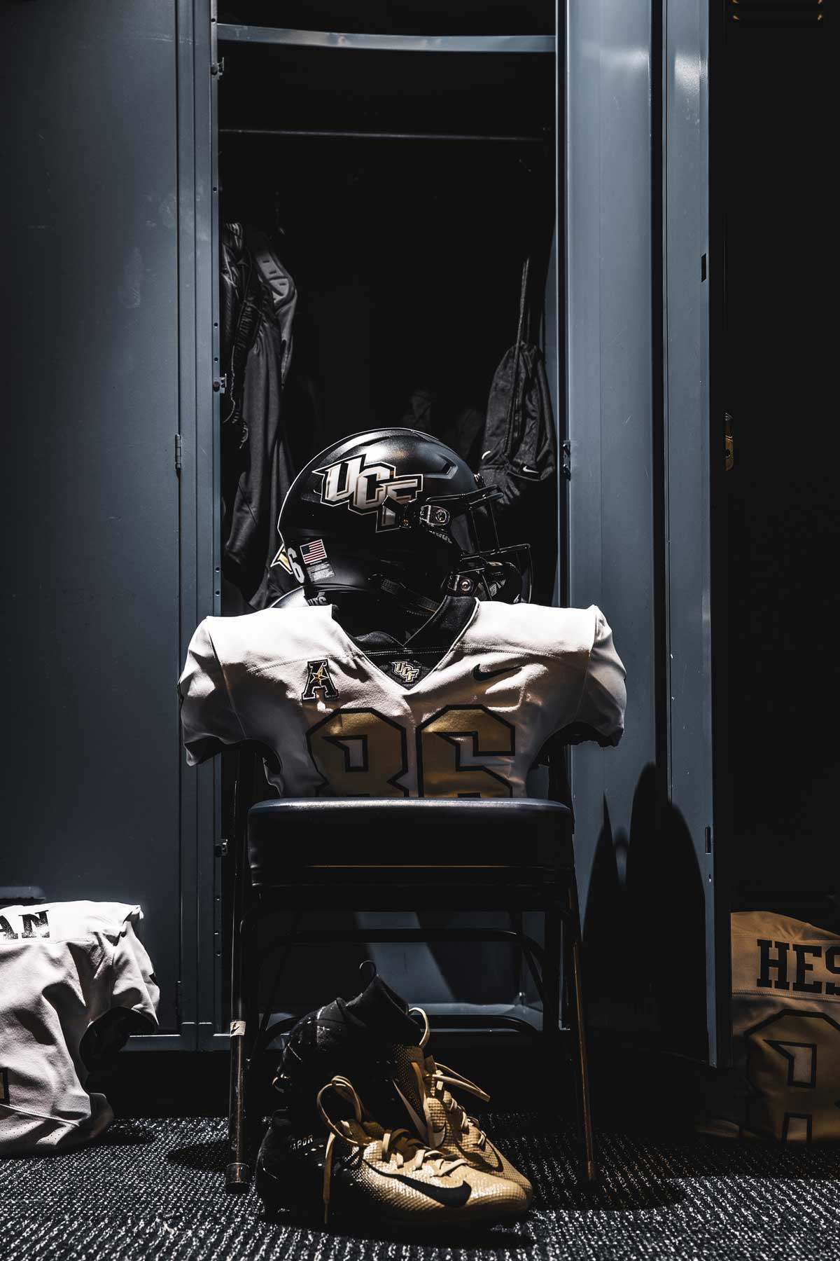 black helmet and white jersey in front of locker
