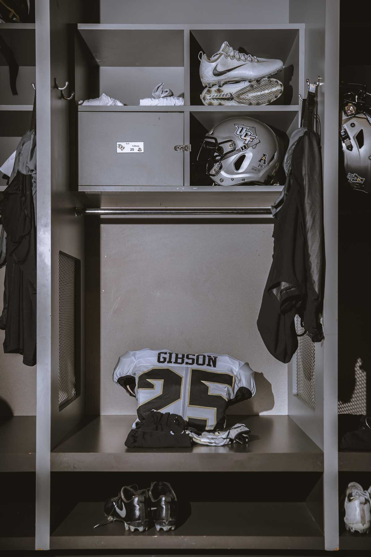 single locker with white football jersey and silver helmet