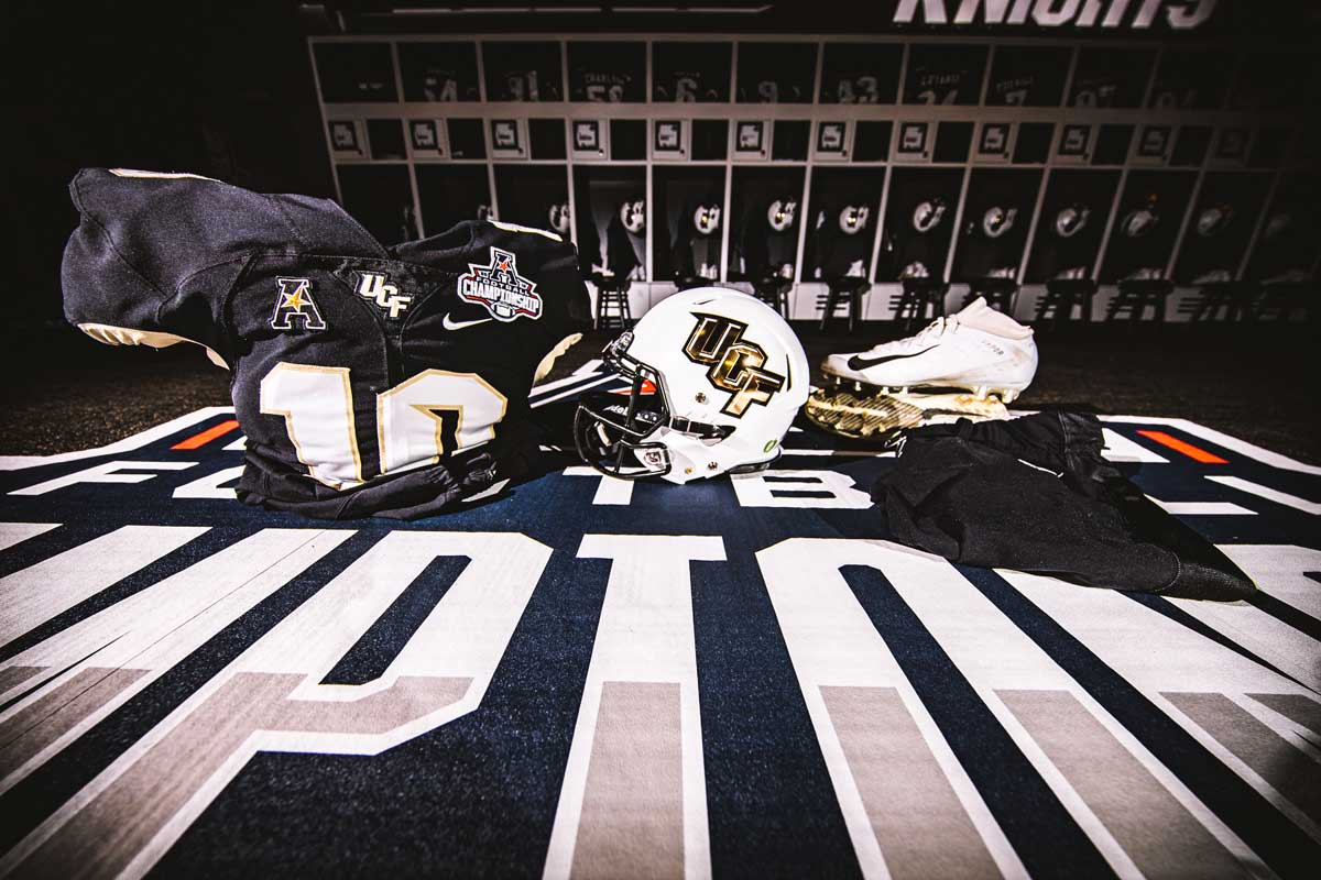 white helmet with gold UCF letters and a black jersey with cleats on a black carpet