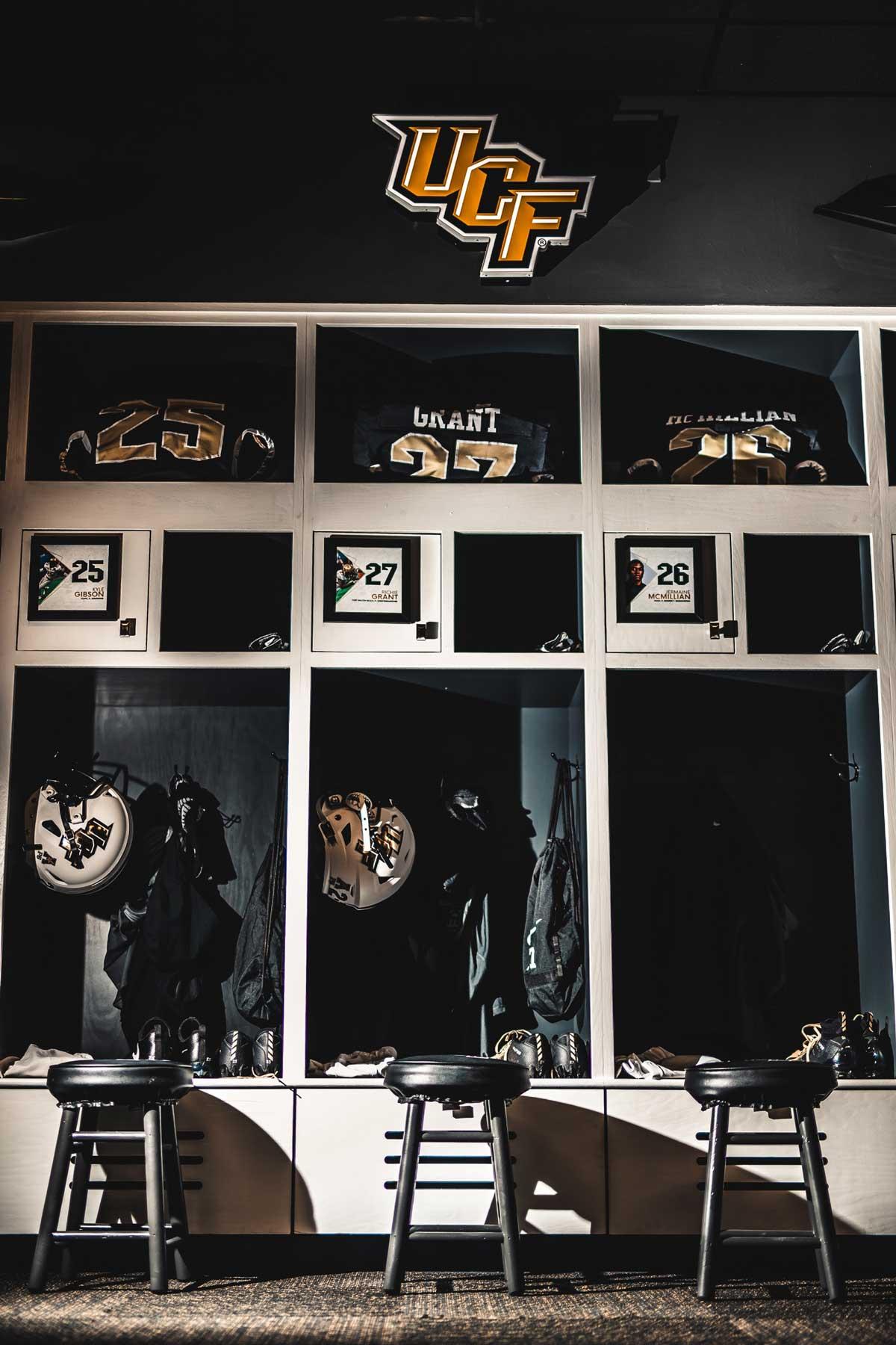 Row of three lockers with white football helmets and black jerseys