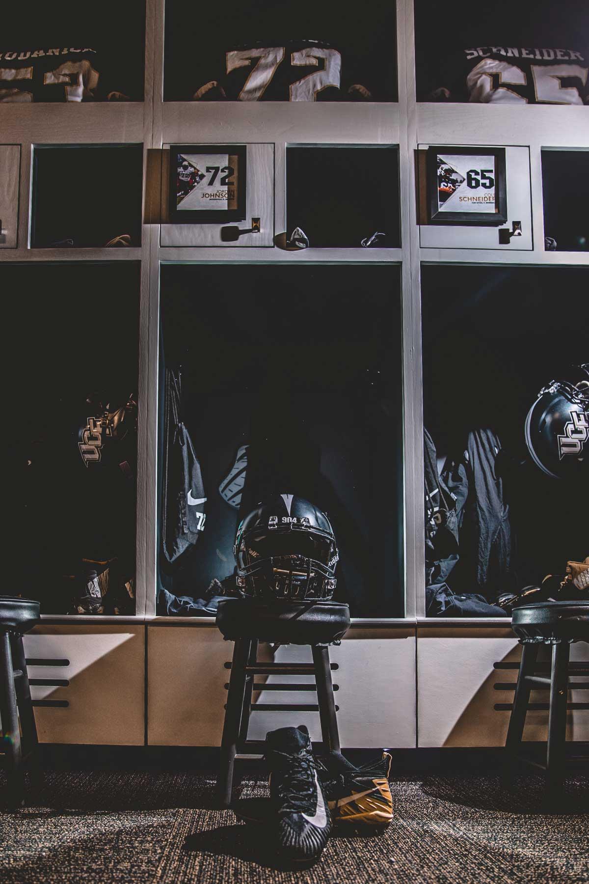 Row of three lockers with black football helmets and jerseys