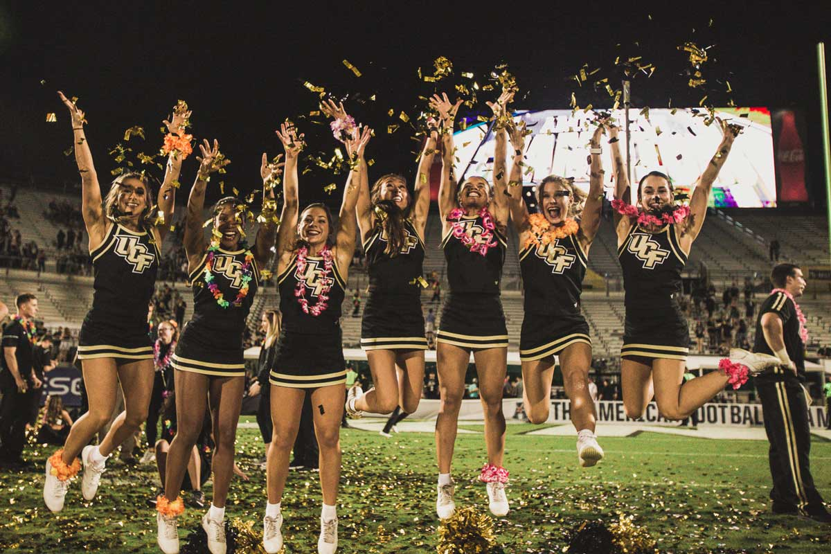 Group of cheerleaders throw confetti while jumping