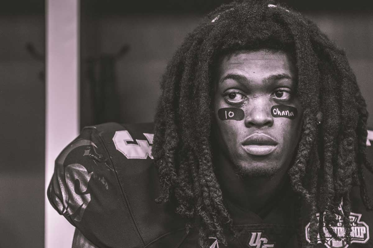 Black and white close up of UCF football player wearing #3 jersey and the message 10 and Ohana on his eye black.