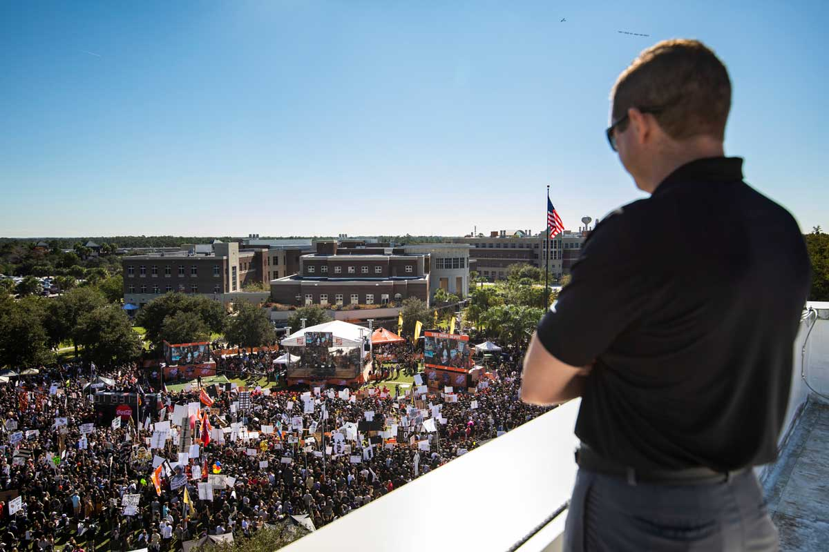 UCF director of athletics Danny White gauzes down from a rooftop at thousands gathered on Memory Mall on a sunny day