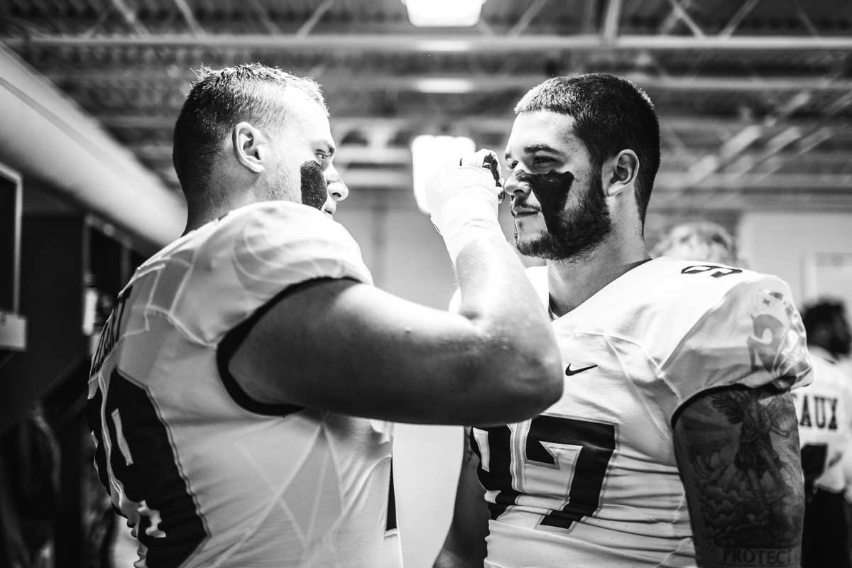 Black and white photo of one football player applying eye black to the face of another player in uniform