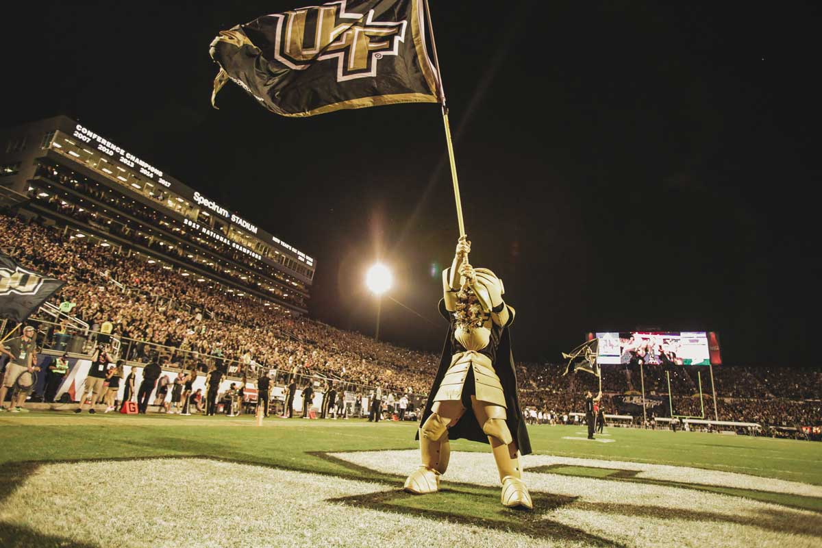 UCF mascot Knightro waves black and gold UCF flag on the field in front of Spectrum Stadium crowd at night