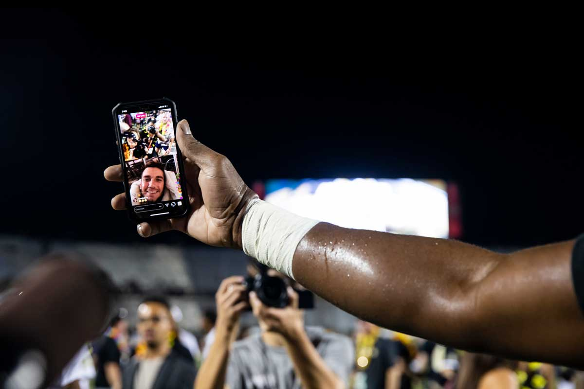 A hand on an outstretched arm grasps a cell phone FaceTiming in quarterback McKenzie Milton to the football field at night