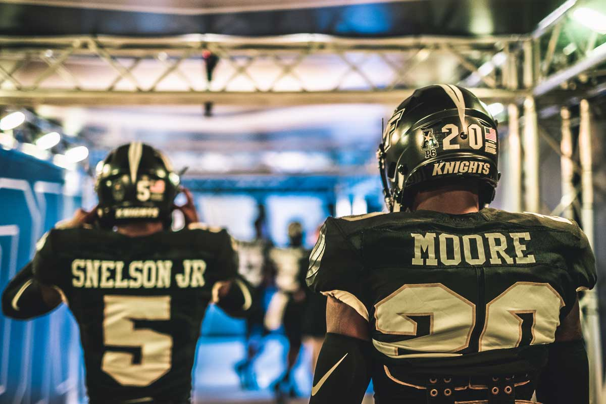 Photo shot from behind as two football players wearing black #5 and #20 jerseys walk in a tunnel under the stadium and head towards the light outside.
