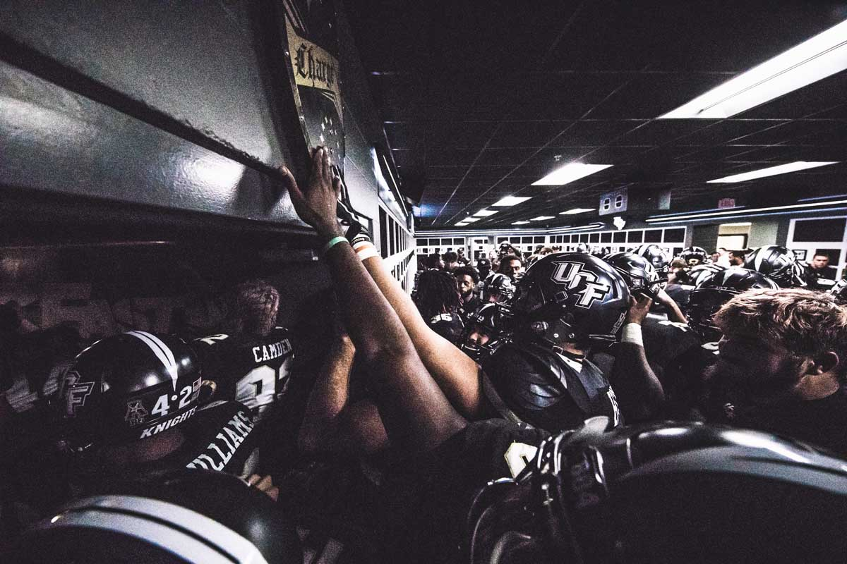 UCF players in full uniform reach up to touch a black and gold shield hanging in their locker room.