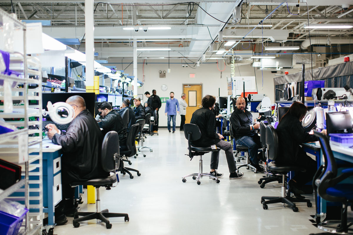 Two rows of workers sit in chairs while they tinker with electronics.