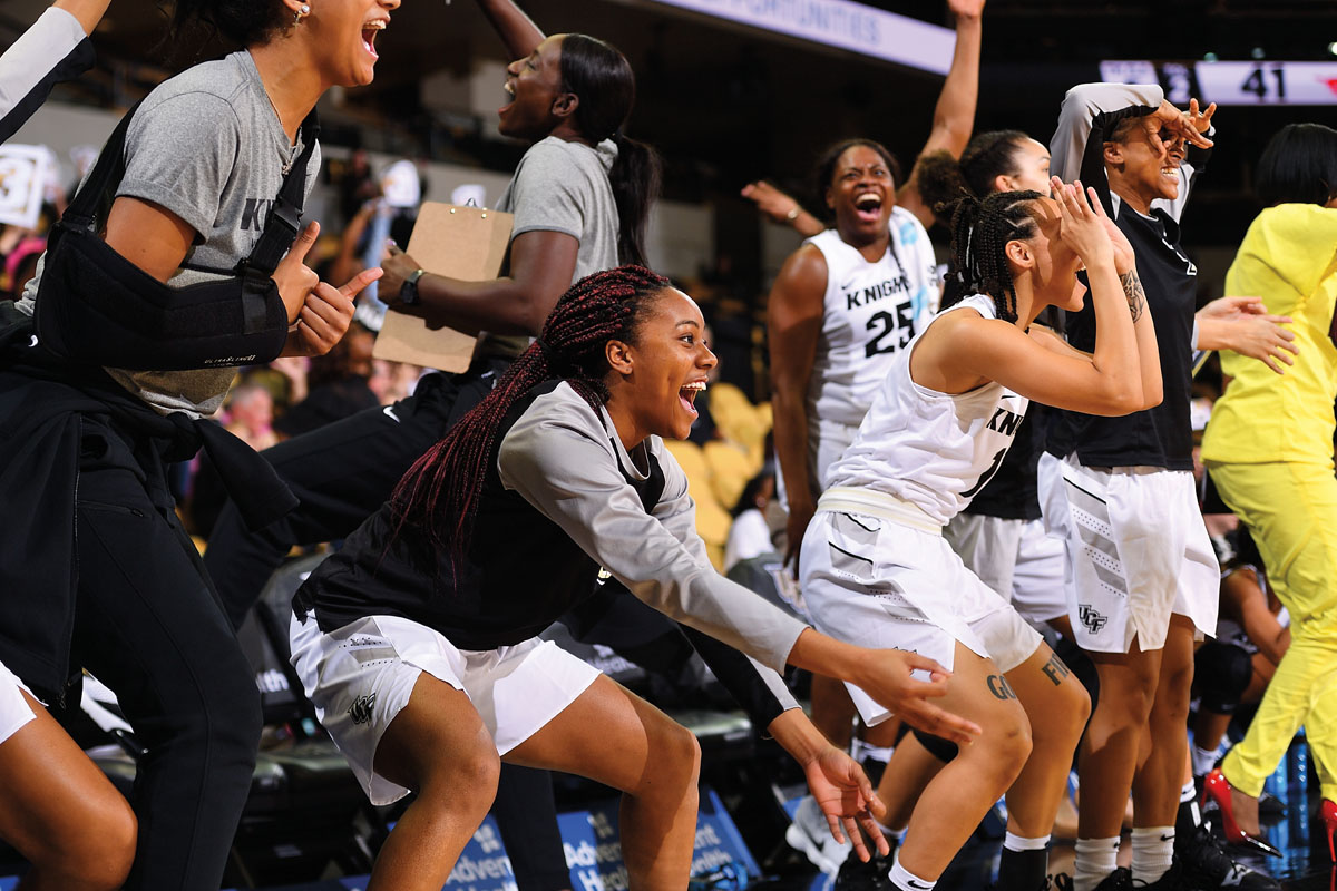 A group of female basketball players cheer.